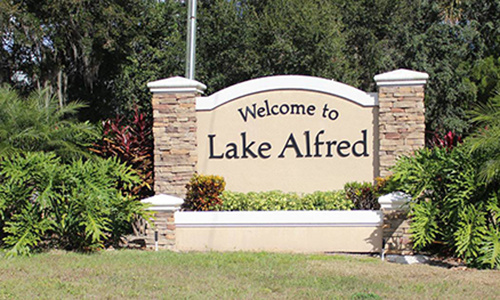 Lake Alfred Welcome Monument surrounded by several green plants and bushes.>