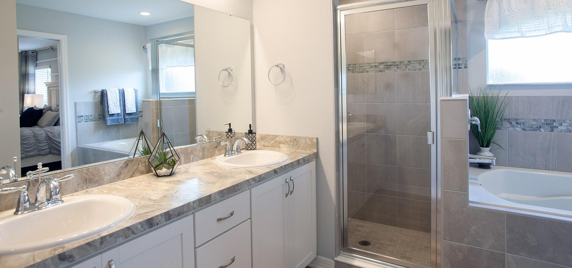 En-suite owner's bath with dual vanities, tub, and shower