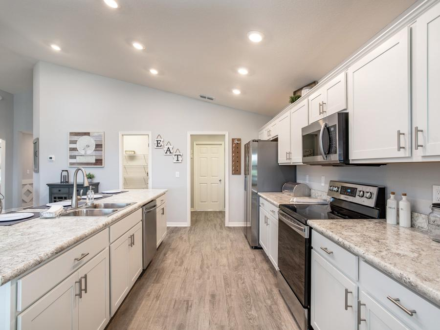 Open kitchen with island and walk-in pantry - VillaMar in Winter Haven, FL